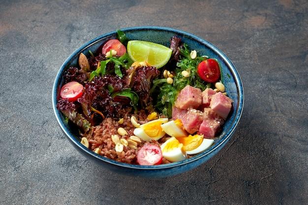 Чаша будды с тунцом, диким рисом, водорослями вакаме и яйцами в синей тарелке.