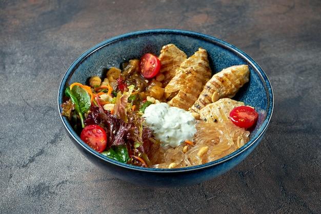 Чаша будды с индейкой, помидорами, овощами и прозрачной рисовой лапшой в синей тарелке. выборочный фокус