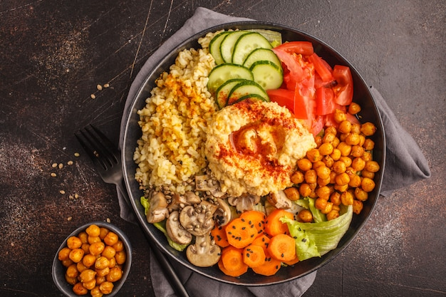 Buddha bowl with vegetables, mushrooms, bulgur, hummus and baked chickpeas. dark background, top view.