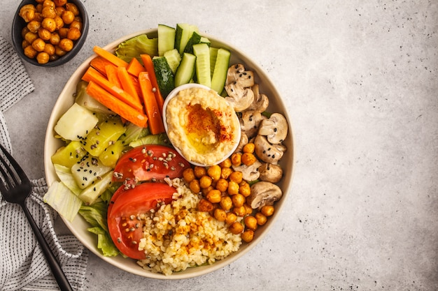 Buddha bowl with vegetables, mushrooms, bulgur, hummus and baked chickpeas. white background, top view.