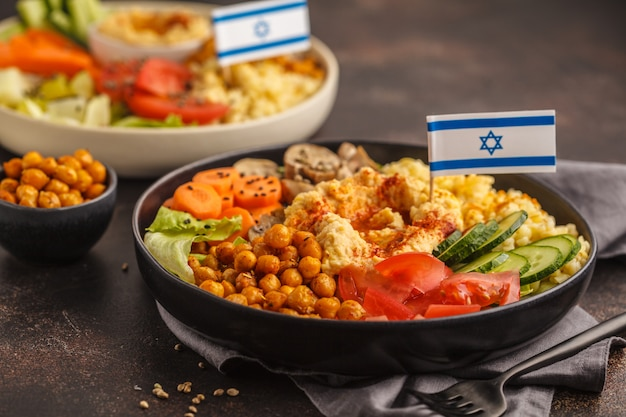 Buddha bowls with vegetables, mushrooms, bulgur, hummus and baked chickpeas. israeli food concept.