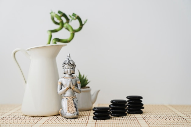 Buddha figure in front of bamboo plant and volcanic stones