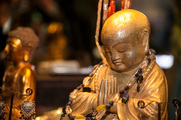 Buddha figure in praying and meditation adorned and surrounded by other spiritual