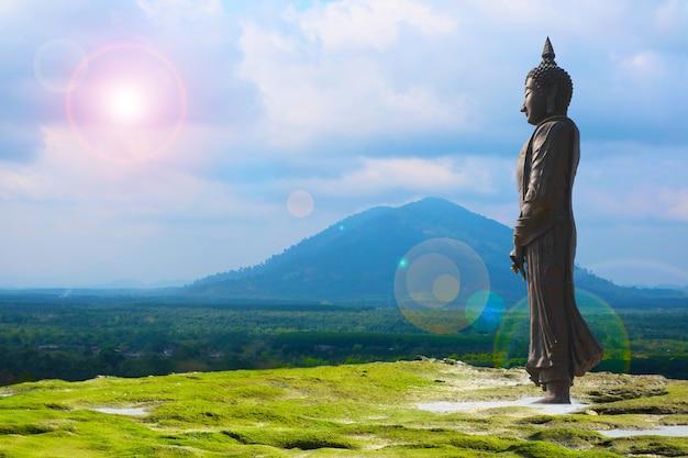 山の背景に7日間のスタイルと太陽の後ろの雲を見ている仏、マカブチャの日は2月または3月に満月の日に開催されます