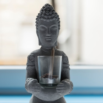 Будда из цемента со стеклом с монетами и карандашом Premium Фотографии