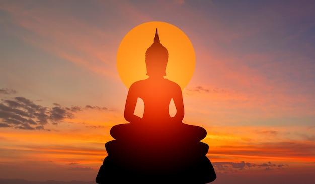 Силуэт будды на золотом закате фона верований буддизма