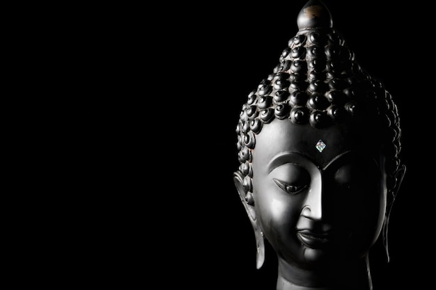 Buddha statue on black background. free space for text