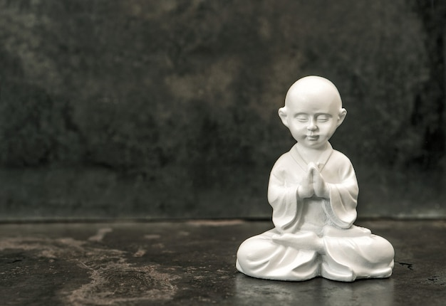 Buddha statue on dark background. praying white monk. meditation concept.  vintage style toned picture