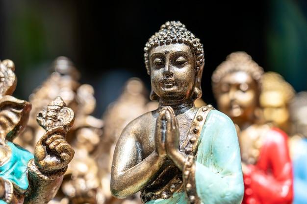 Сувенирные фигурки статуи будды выставлены на продажу на уличном рынке в убуде, бали, индонезия. ремесла и дисплей сувенирного магазина, крупным планом