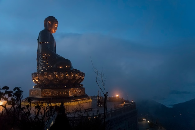 Buddha statue in the midst of the fog on the top of fansipan mountain, vietnam. buddha statue on top at sunset in the clouds.