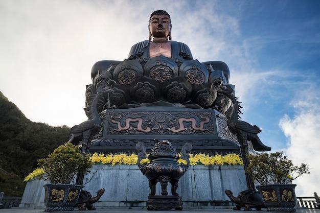 雲の中で日没時に上に仏像。ベトナム、ラオカイ、サパのファンシパン山の頂上にある大きな仏像。壮大なファンシパンの伝説