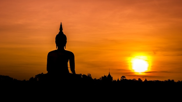 Buddha statue over scenic sunset sky background