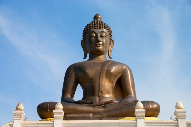 Buddha statue in temple with blue sky background.