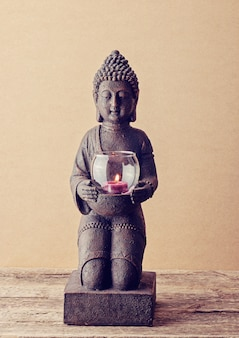 Buddha statue with a burning candle in his hands