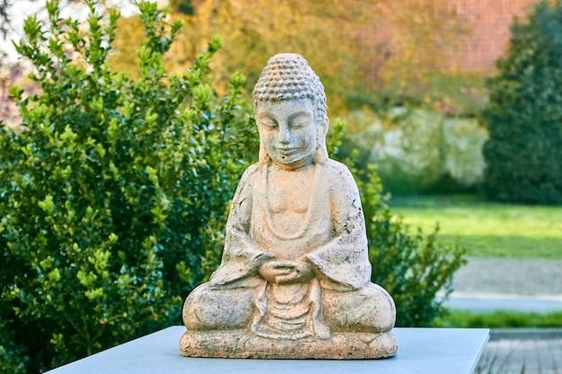 Статуя будды с закрытыми глазами в позе лотоса