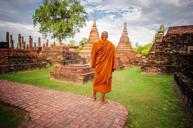 Buddhist monk in ancient ruins in ayutthaya, thailand.