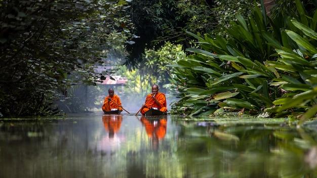 Буддийский монах в маленькой деревянной лодке плывет по каналу