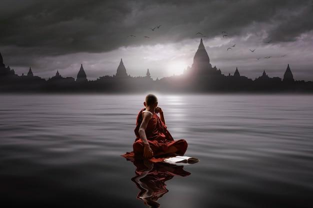 물에 앉아 사원을 바라 보는 스님
