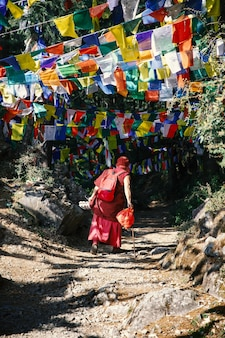 A buddhist monk walks surrounded by colorful tibetan prayers flags toned photo