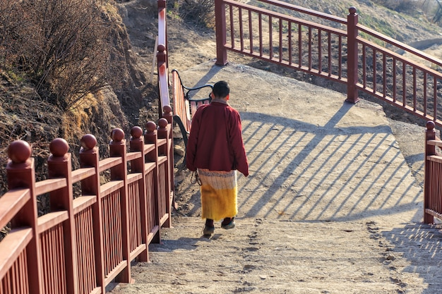 Buddhist nun walking down stairway at larung gar in a warm and foggy morning time, sichuan