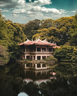 Buddhist temple over the lake surrounded by trees, shinjuku gyoen national garden, tokyo