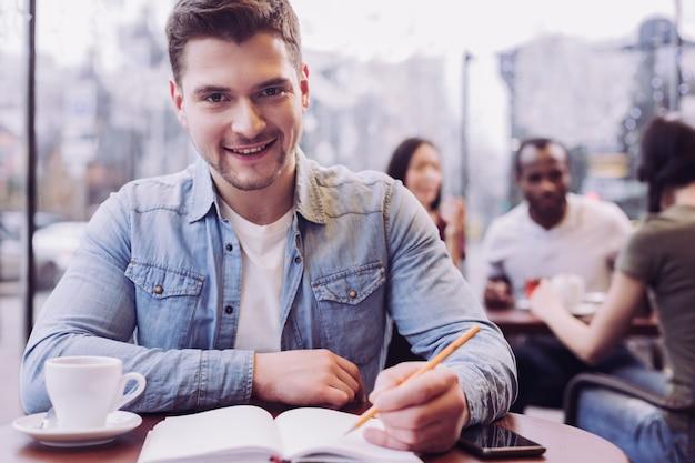 Подающий надежды очаровательный студент-мужчина держит карандаш за чашкой кофе