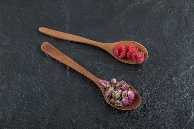 Rose in erba e lamponi su cucchiai di legno.