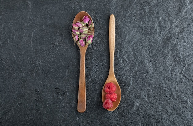 Budding roses and raspberries on wooden spoons.