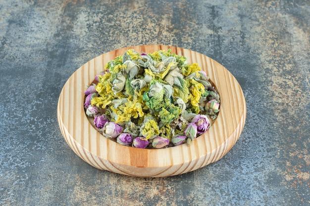 Rose in erba e fiori gialli sul piatto di legno.