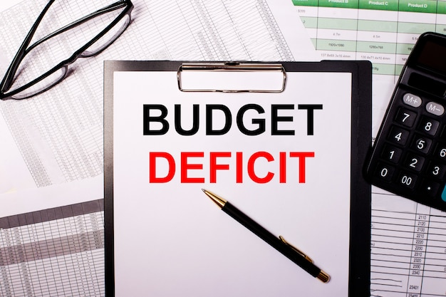 予算の赤字は、眼鏡と電卓の近くの白い紙に書かれています。