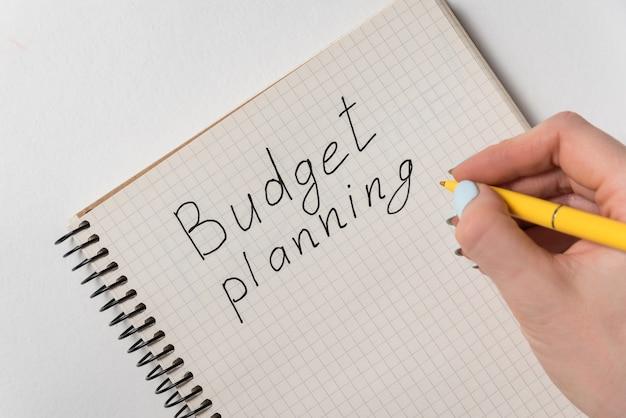 Планирование бюджета, написанное на ноутбуке на белой поверхности Premium Фотографии
