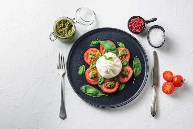 신선한 토마토와 바질을 곁들인 버팔로 부라 타 치즈는 검은 접시에 페스토 소스를 남깁니다.