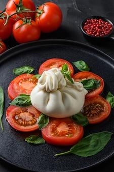 신선한 토마토와 바질 잎을 곁들인 버팔로 부라 타 치즈