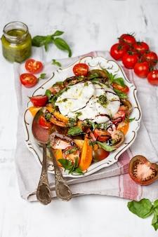 新鮮な生トマトとバジルの葉を添えたバッファローブッラータチーズ