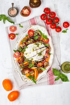 Buffalo burrata cheese with fresh raw tomatoes and basil leaves