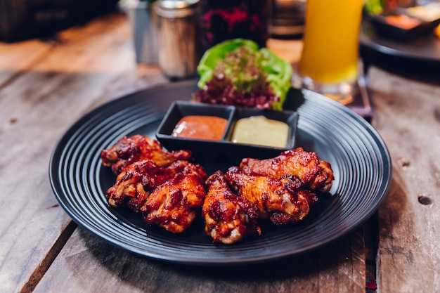 Buffalo chicken wings served with mayonnaise and thousand island sauce in black plate.
