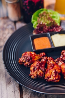 Buffalo chicken wings served with mayonnaise and thousand island sauce in black plate