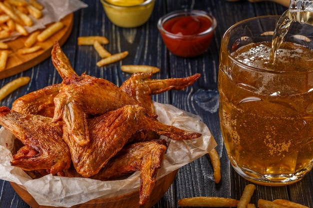 Buffalo wings with french fries and beer.