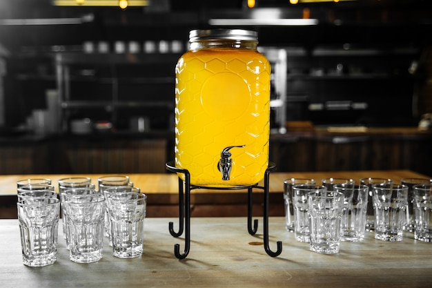 机の上のガラスが付いているビュッフェフルーツ黄色レモネード瓶