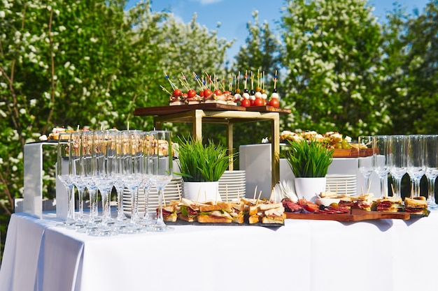 Шведский стол на свежем воздухе - стол с канапе и бокалами на фоне цветущих деревьев и неба.