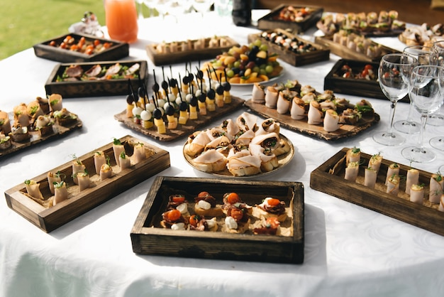 The buffet at the reception. assortment of canapes on wooden board. banquet service. catering food, snacks with cheese, jamon, prosciutto and fruit