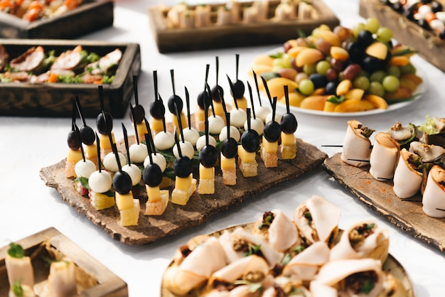 The buffet at the reception. assortment of canapes on wooden board.