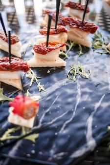 さまざまな軽食やサンドイッチを備えた宴会でのゲストのためのビュッフェテーブル