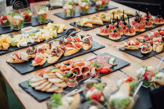 Buffet table of reception with cold snacks, meat and salads