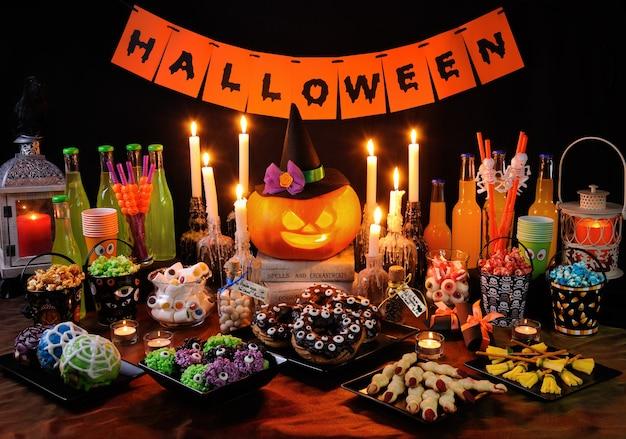 ハロウィーンに敬意を表して調理され、装飾されたお菓子や飲み物のビュッフェテーブル
