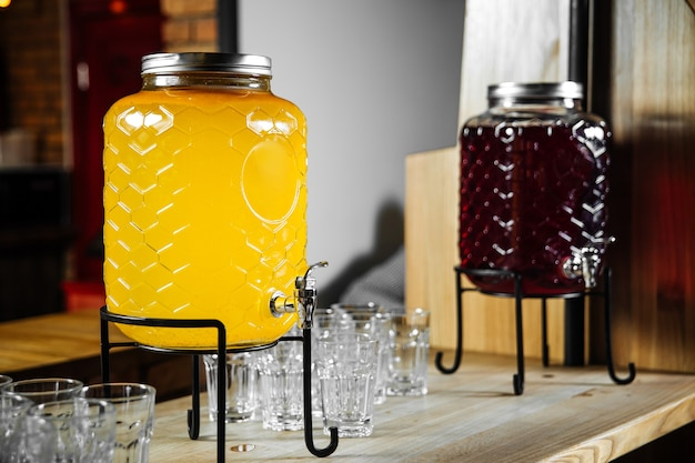 Buffet variety of lemonade jars with glasses on the desk