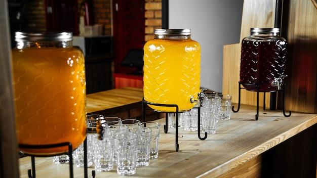 Шведский стол из банок лимонада со стаканами на столе