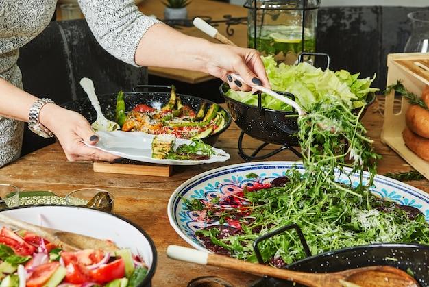 野菜料理とサラダの豊富な品揃えのビュッフェ、女性は皿にサラダを選ぶ