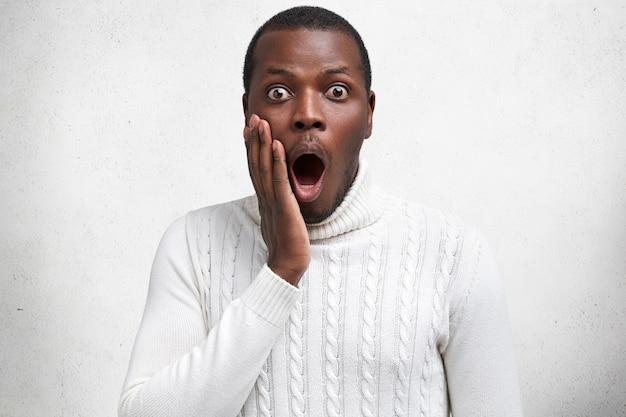 Жукоглазый темнокожий эмоциональный самец с широко открытым ртом удивляется, держит вывалившуюся челюсть, понимает, что на его счету нет денег