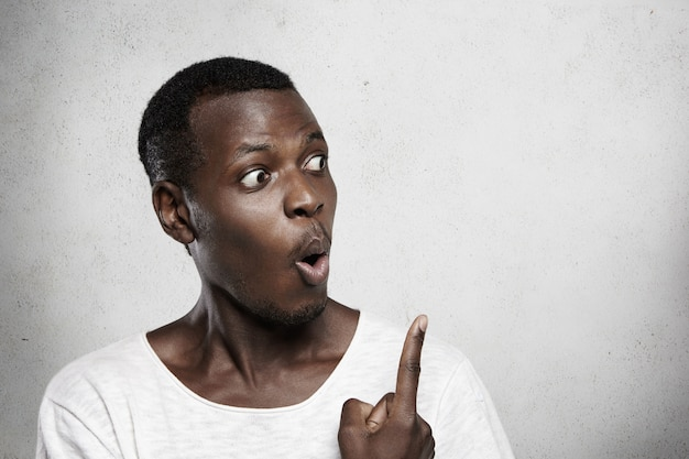 Bug-eyed dark-skinned man with amazed and astonished expression, looking at blank wall, showing copy space for your information, pointing his index finger.